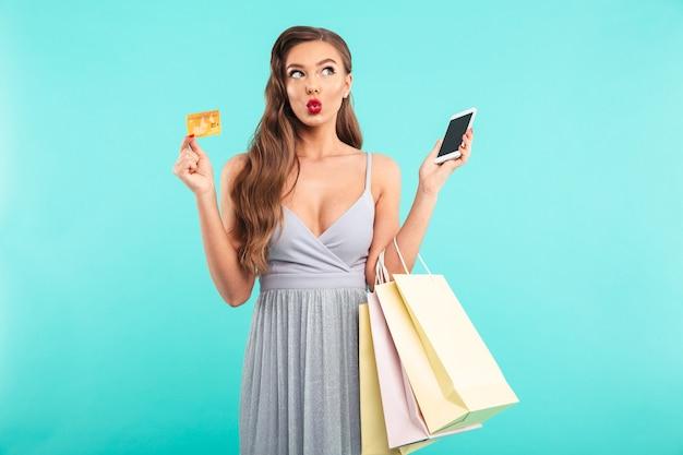 Charmante shopaholic vrouw met boodschappentassen en betalen met smartphone en creditcard, geïsoleerd over blauwe muur