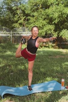 Charmante sportieve vrouw met lang haar die zich uitstrekt in het park voordat ze gaat joggen