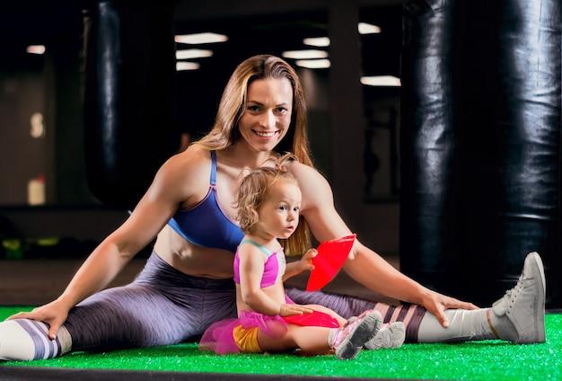 Charmante sportmoeder traint in de sportschool met haar dochtertje en een franse bulldog. gemengde media