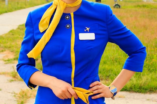 Charmante stewardess gekleed in uniform buiten wachtend op haar vlucht