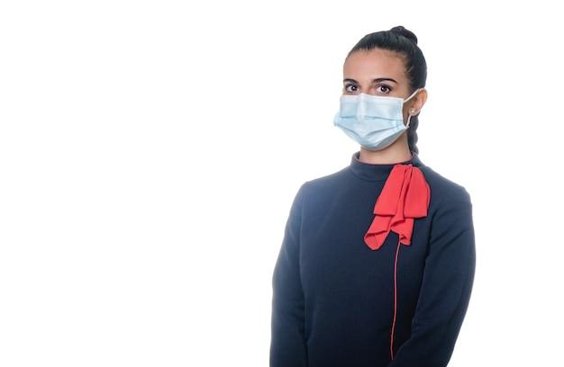 Charmante stewardess met gezichtsmasker die in uniform draagt. geïsoleerd op witte achtergrond.