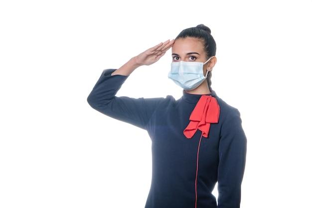 Charmante stewardess met gezichtsmaskergroet die in uniform draagt. geïsoleerd op witte achtergrond.