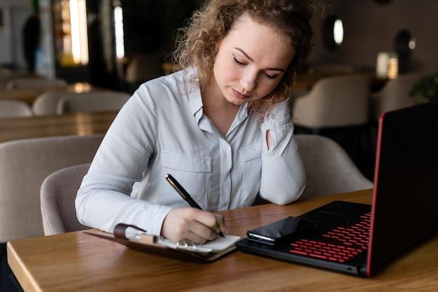 Charmante student bladert informatie op een laptop die is verbonden met 4g-internet.