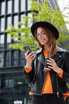 Charmante student boekt hotel online, heeft reis in de grote stad, gericht op smartphone