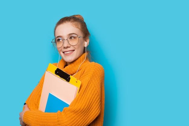 Charmante student met rood haar en sproeten luisteren naar muziek via een koptelefoon en enkele boeken op een blauwe muur te houden