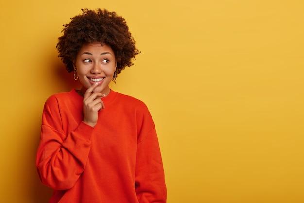 Charmante tedere krullende vrouw glimlacht blij, kijkt opzij, draagt vrijetijdskleding, staat tegen gele studiomuur