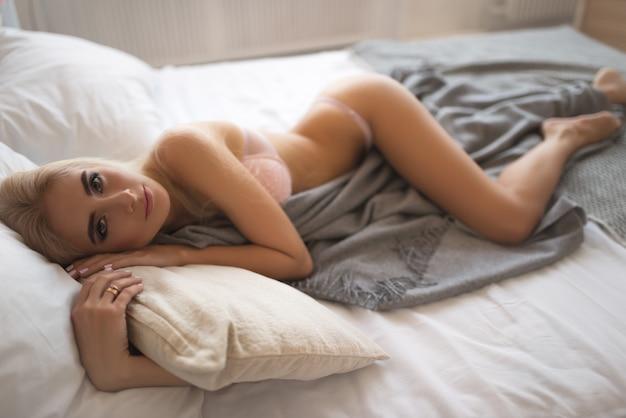Charmante tedere vrouw ligt in beddengoed en geniet van een warm, comfortabel bed.