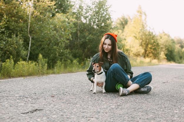 Charmante tiener meisje zit met haar hond op de weg.