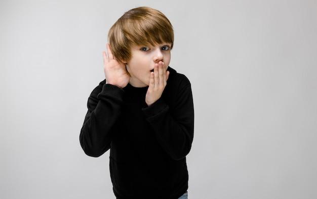 Charmante tiener met blond haar en donkere ogen. de jongen sluit zijn mond met één hand, brengt zijn andere hand naar zijn oor