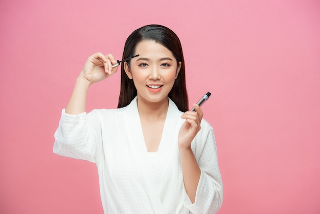 Charmante tienermeisjesvrouw die mascara/photoset van aantrekkelijk meisje op roze achtergrond toepast