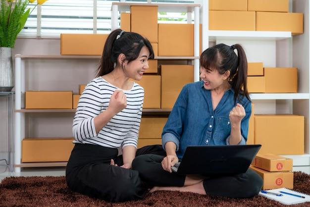 Charmante twee aziatische tiener eigenaar zakenvrouw werken thuis voor online winkelen, kijken en opgewonden om laptop en met kantoorapparatuur, ondernemer lifestyle concept