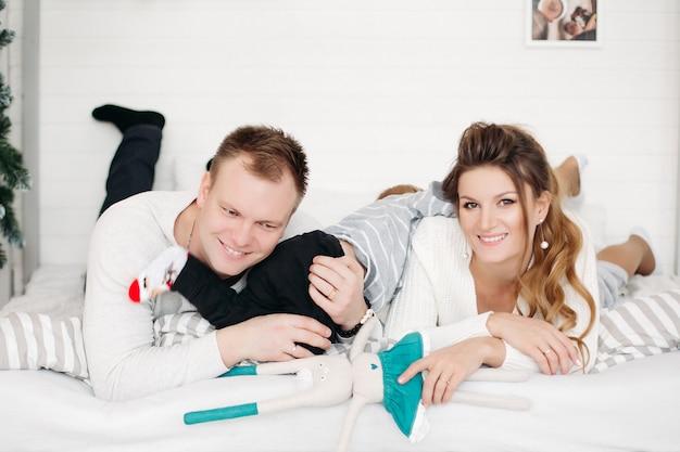 Charmante vader en moeder met kleine schattige zoon samen op bed liggen, voorzijde kijken en poseren in de studio in de winter