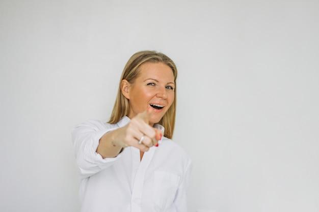 Charmante veertig jaar blonde lange haarvrouw die vinger naar camera, selectieve nadruk trekt