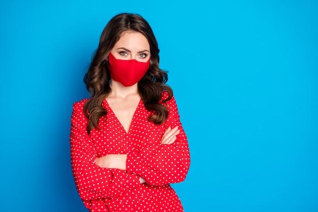 Charmante verantwoordelijke brunette dame draagt een rood medisch masker met gekruiste armen