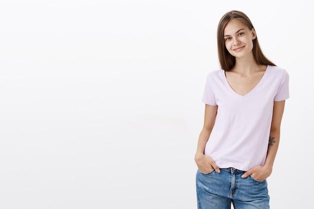 Charmante verlegen en schattige europese jonge vrouwelijke brunette in casual blouse staande met handen in zakken hoofd kantelen en lachend met vriendelijke blik nieuwe collega's leren kennen
