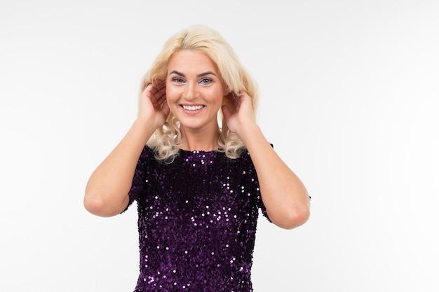 Charmante verrast blond meisje in paarse mooie elegante jurk op een witte achtergrond met kopie ruimte