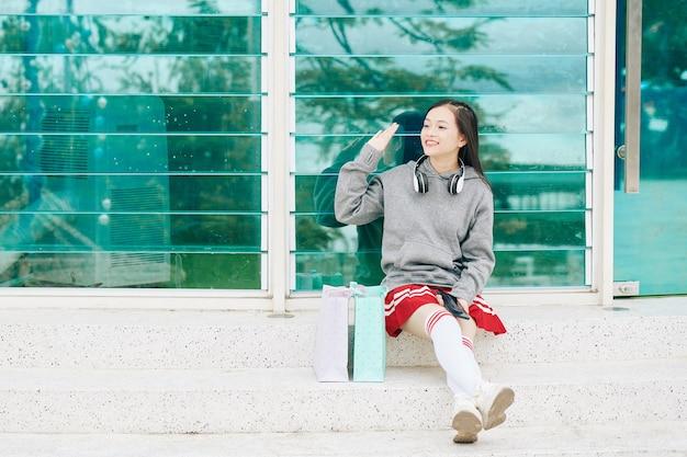 Charmante vietnamese tienermeisje zittend op stappen voor winkelcentrum en zwaaien met de hand