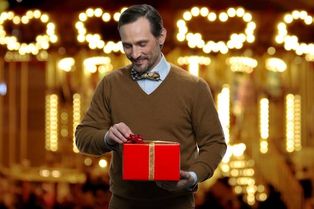 Charmante volwassen man opent kerstcadeau. vader maakt rode geschenkdoos met gouden lint los.