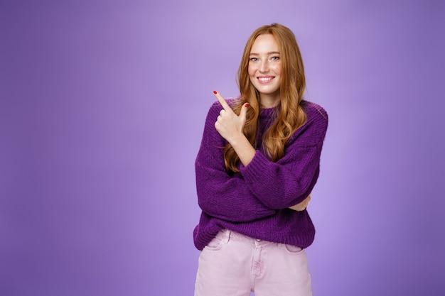 Charmante, vriendelijk ogende, heldere roodharige vrouw met sproeten en make-up in een paarse warme trui die naar de linkerbovenhoek wijst en blij en schattig glimlacht naar de camera als een koele plek om rond te hangen.