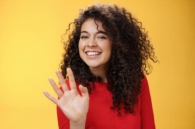 Charmante vriendelijke en zelfverzekerde aantrekkelijke gekrulde vrouw die schattig met palm zwaait om hallo of hallo te zeggen glimlachend breed groetende man probeert flirt in partij vrolijk poseren over gele achtergrond.