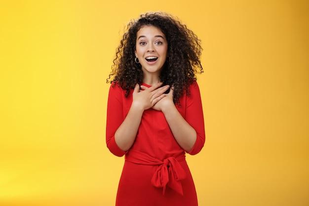 Charmante vriendin die een nieuwjaarscadeau ontvangt, voelt zich gelukkig en verrast, hand in hand op de borst, zuchtend en breed glimlachend van verbazing, dankbaar en blij over de gele muur.