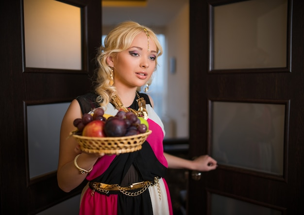 Charmante vrij jonge vrouw met krullend haar en gouden juwelen