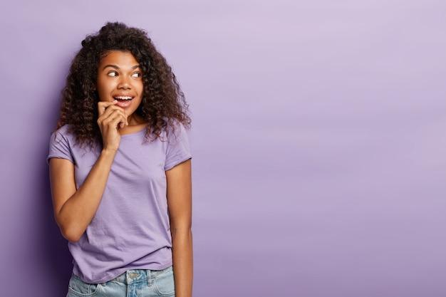 Charmante vrolijke afro-amerikaanse vrouw zonder make-up, heeft natuurlijke schoonheid, geniet van goed gezelschap, kijkt weg