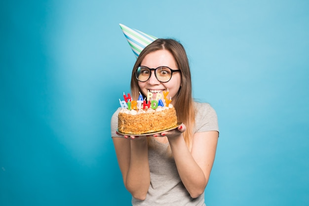 Charmante vrolijke gekke jonge studente die in felicitatiedocument hoed een gelukkige verjaardagstaart houdt