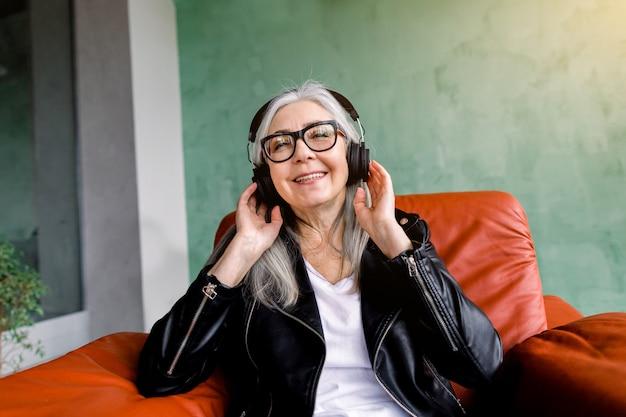 Charmante vrolijke gelukkig senior dame met lang grijs haar, gekleed in een stijlvolle zwarte leren jas, zittend in rode fauteuil op groene achtergrond