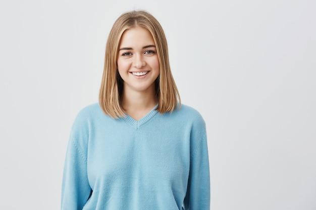 Charmante, vrolijke, glimlachende europese vrouw met een aantrekkelijk uiterlijk en blond haar met een blauwe trui die haar perfecte tanden laat zien met een goed humeur en geniet van het poseren.