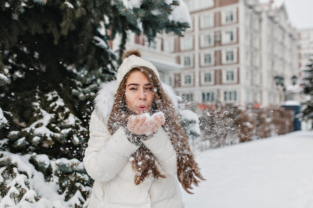 Charmante vrolijke vrouw waait sneeuwvlokken uit haar handen in de winterdag buiten op straat.