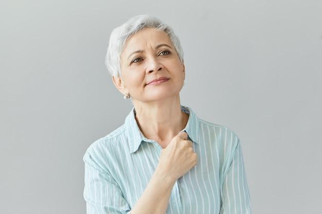 Charmante vrolijke vrouwelijke gepensioneerde die stijlvolle kleding draagt die de hand op haar borst houdt, omhoog kijkt, nostalgie heeft naar oude tijden, herinneringen opdoet, dagdroomt, een dromerige, tevreden gezichtsuitdrukking heeft
