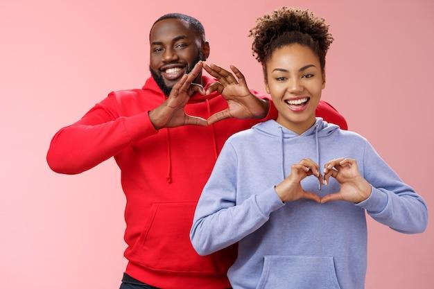 Charmante vrolijke zorgzame jonge afro-amerikaanse familie man vrouw broers en zussen glimlachend breed tonen hart gebaren grijnzend uitdrukken liefde empathie positiviteit, twee loyale vrienden koesteren vriendschap