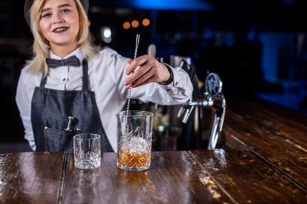 Charmante vrouw barman legt de laatste hand aan een drankje in de nachtclub