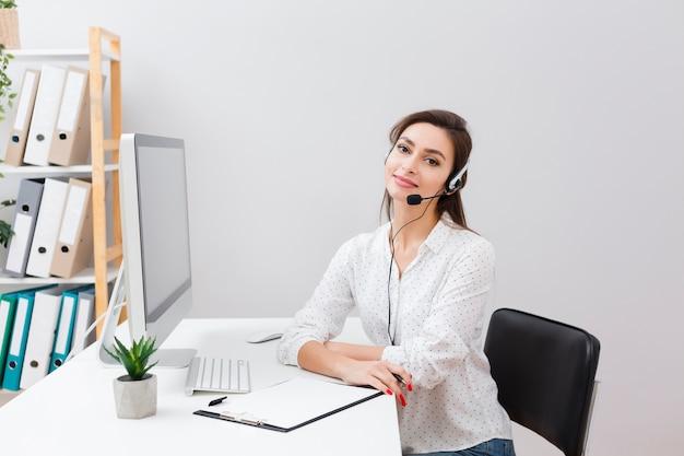 Charmante vrouw bij bureau dat hoofdtelefoon draagt