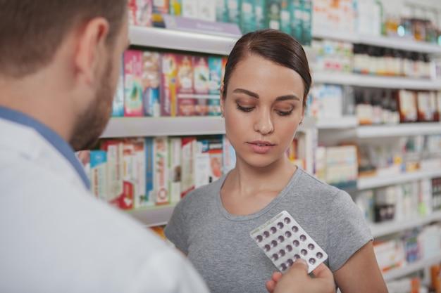 Charmante vrouw die bij apotheek winkelt