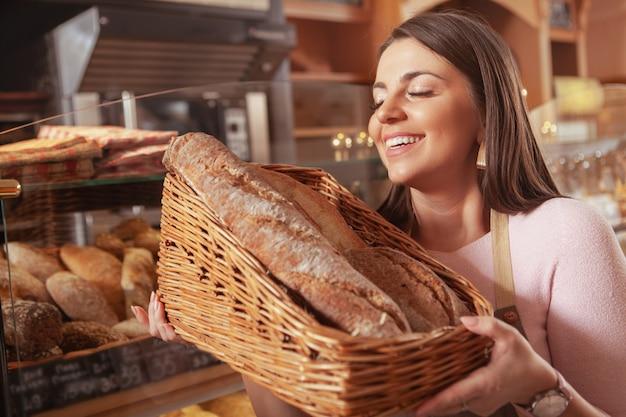 Charmante vrouw die bij haar bakkerijwinkel werkt