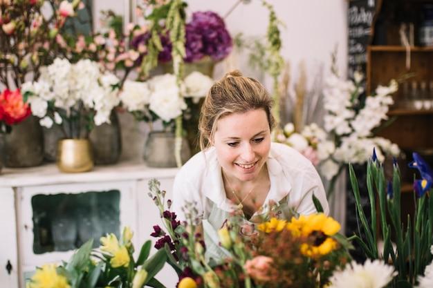 Charmante vrouw die bloemstukken maakt