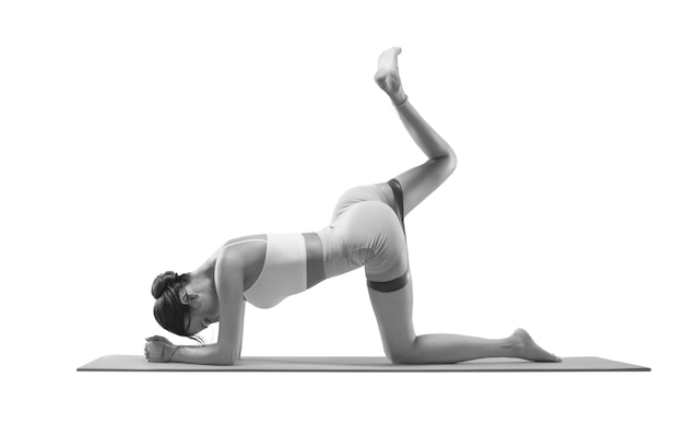 Charmante vrouw die een oefening doet om de achterkant van de dij te pompen met een elastische band. geïsoleerd op wit. het concept van sport, fitness, pilates, bodybuilding.