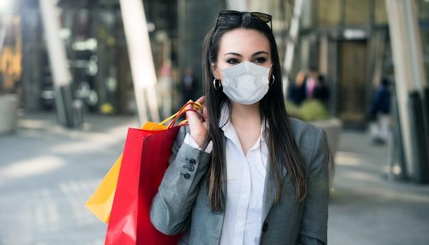 Charmante vrouw die in een stadsstraat loopt met boodschappentassen, covid- of coronavirusconcept