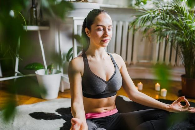 Charmante vrouw die in installaties mediteert