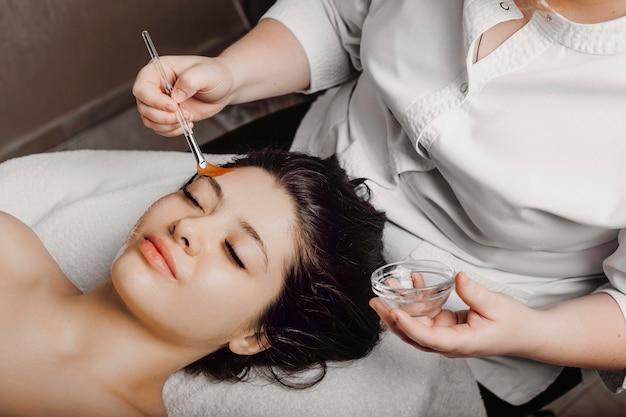 Charmante vrouw die op een kuuroordbed met gesloten ogen leunt die een antiverouderingsmasker met hyaluronzuur in een wellnesskuuroord doen.