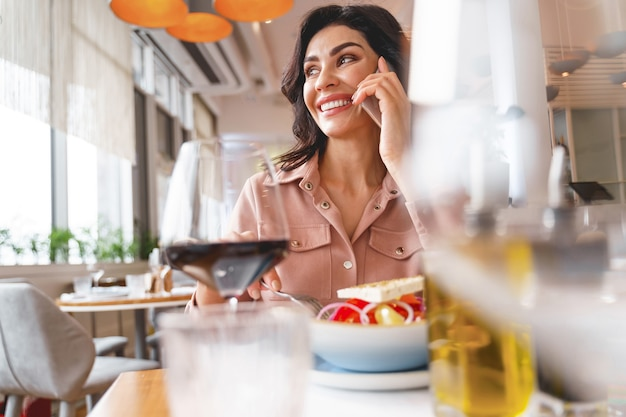 Charmante vrouw die op mobiel praat en glimlacht terwijl ze aan tafel zit met eten en wijn
