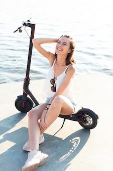 Charmante vrouw die zich voordeed op scooter