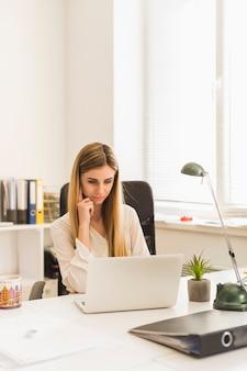 Charmante vrouw doorbladerende laptop in bureau