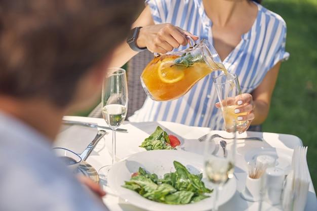 Charmante vrouw en man rusten tijdens de lunch terwijl ze een smakelijke maaltijd eten en koud water drinken