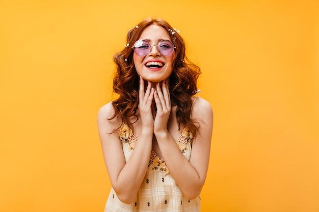 Charmante vrouw gekleed in een geruite top lacht. schot van roodharige vrouw in lila glazen.