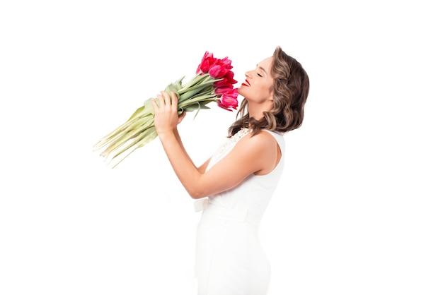 Charmante vrouw gekleed in wit ruikende bos roze tulpen