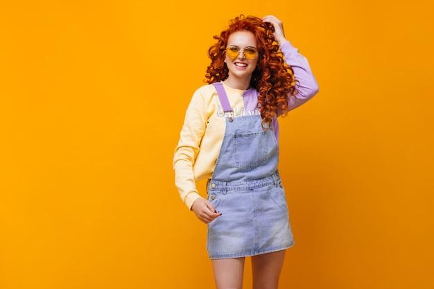 Charmante vrouw in blauwe jumpsuit en bril lacht op oranje muur