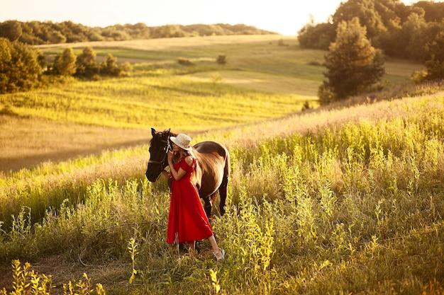 Charmante vrouw in een hooi hoed en rode jurk staat met een paard op het groene veld